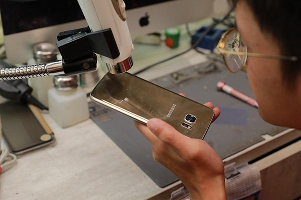 移除sim卡卡槽,接著使用加熱槍軟化手機內部膠。三星手機維修
